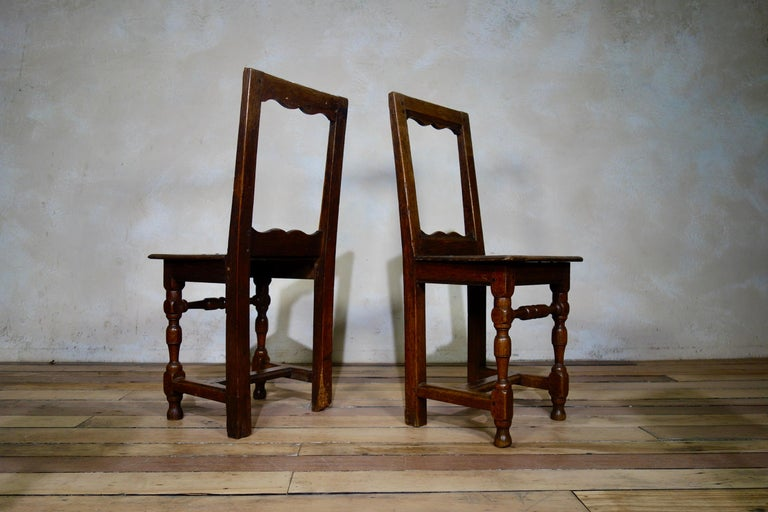 A set of four backstool chairs, featuring a matching pair with a further two chairs, similar in style. Demonstrating open backs above solid seats, turned and block supports and H-stretchers.  Please note that all chairs vary slighlty in size.