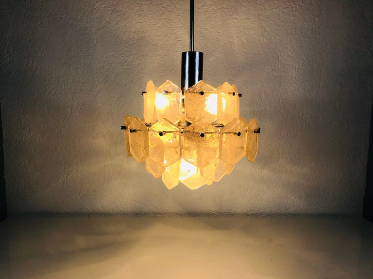 A Kalmar Franken ice glass chandelier made in Austria in the 1960s. It is fascinating with its rare glass shapes. Four-tier chandelier with hexagonal ice glasses. The glasses are secure to the metal frame with cylinder shaped chrome screws.
