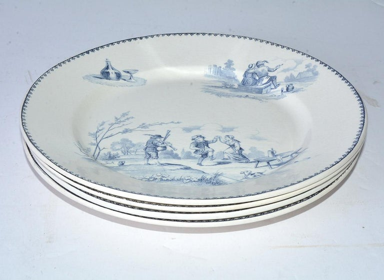 The four charming dinner plates have blue country scenes on cream