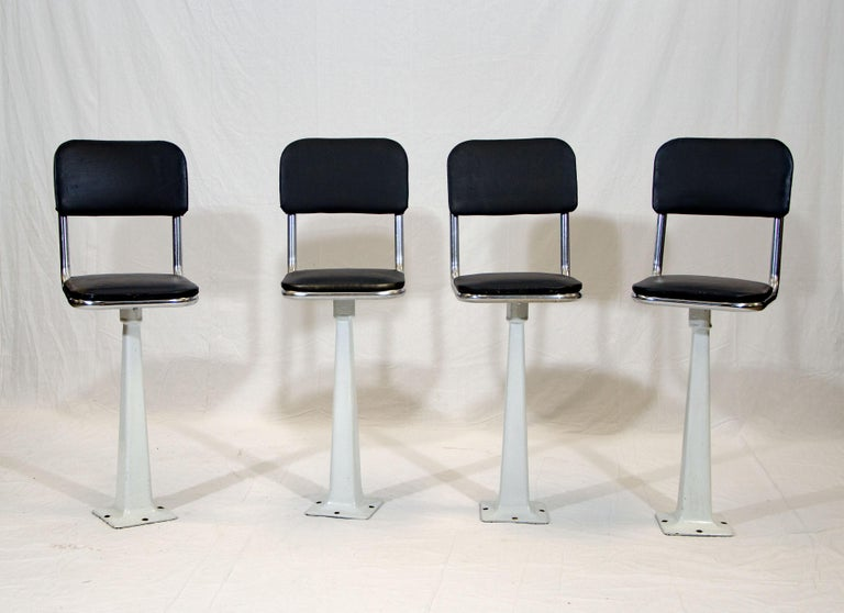 These have cast iron bases with a white porcelain finish. and original seats and backs that have a sprayed black finish on vinyl. One back is not quite as curved as the other three. The seats and backs are attached to a chrome frame. The seats are