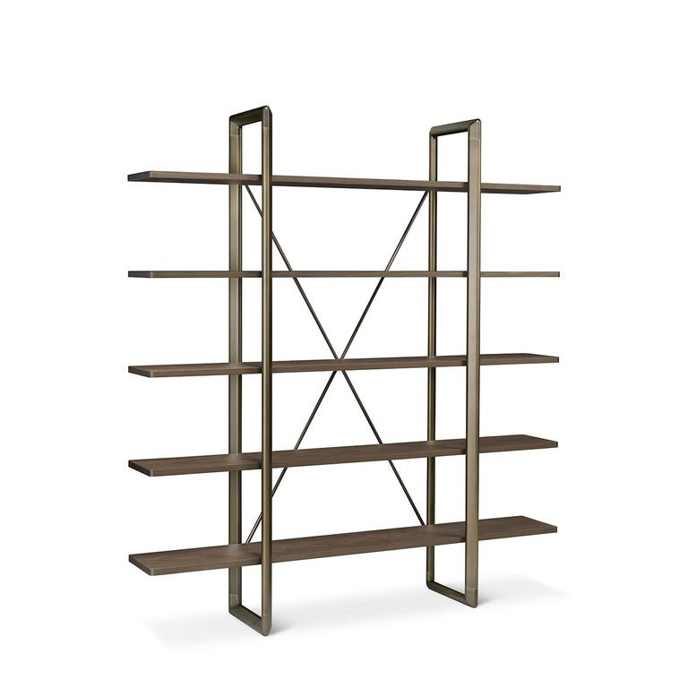 A clean and essential design of strong geometrical value, this striking bookcase will make a bold and stately addition to any contemporary decor. Featuring two vertical supports and a crisscrossed back in brass, it is composed of five open shelves