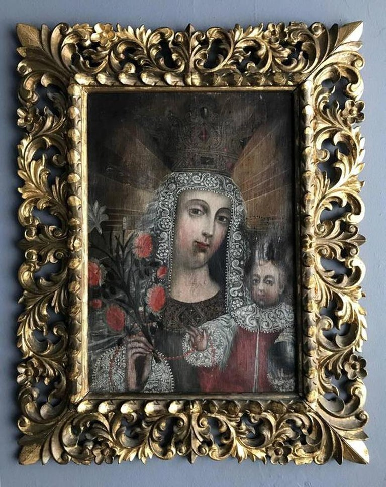 A lovely antique Peruvian oil on linen painting from Spanish Colonial period late 18th-early 19th century. In the style of Classic Cuzco School, the painting depicts Madonna and Baby Christ and were heavily embellished with symbols of Christianity