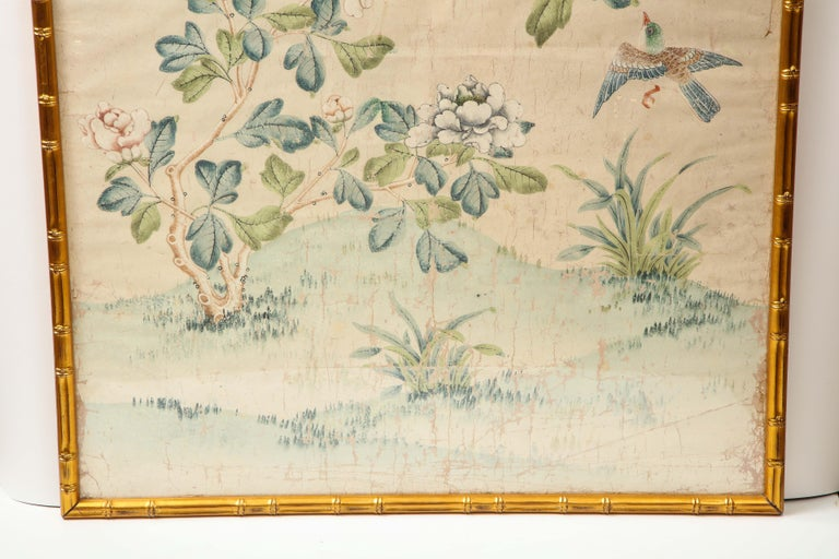 A stunning hand painted wallpaper panel by Gracie in a giltwood faux bamboo frame. The lovely scene is composed of branches, flowers, birds and butterflies in soft, muted tones. This piece could inspire the colors used in a room and is a great way