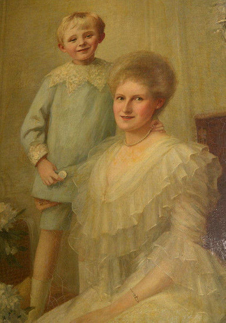 A charming framed Edwardian oil on canvas portrait of a mother and son in a drawing room setting.  The mother seated with her young son standing behind, both beautifully attired.  A mahogany cabinet bearing a silver candelabra sits to the right