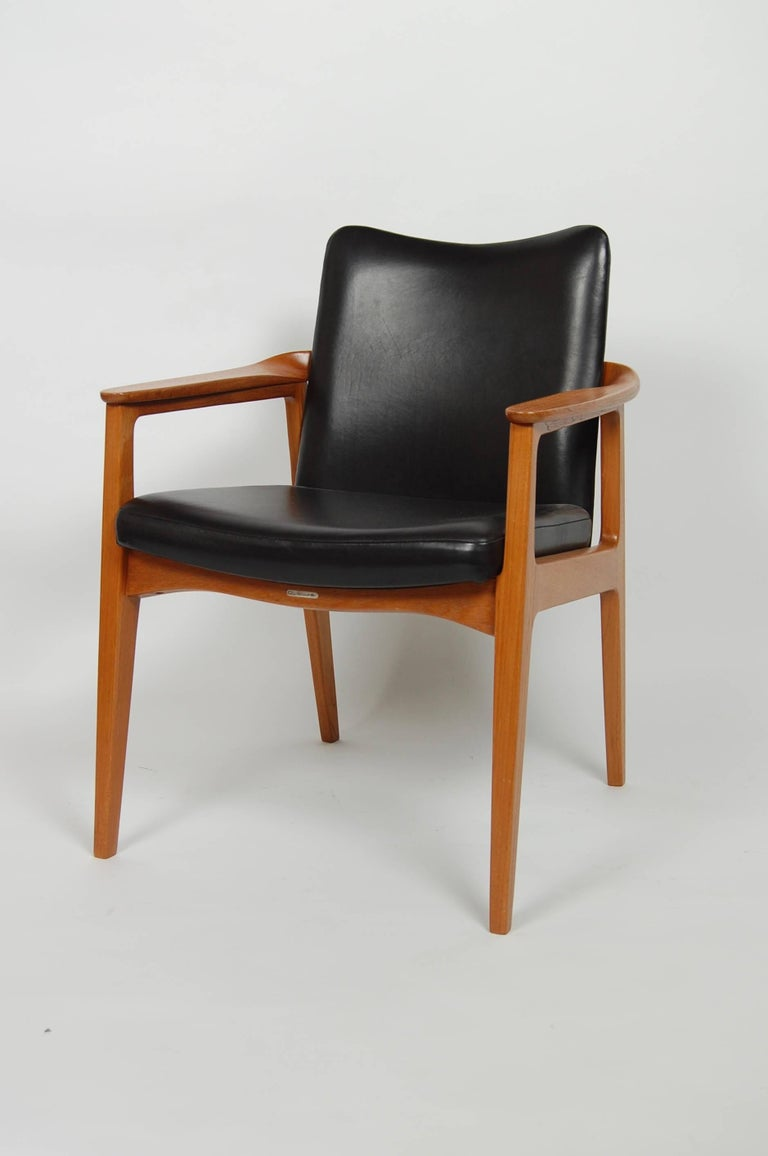 1950s solid teak and newly upholstered in black leather chair by France & Sons, imported by art collector John Stewart of John Stewart Inc, NY and designed by Sigvard Bernnadotte. Wrap around arms with nice joinery details and a curved back which