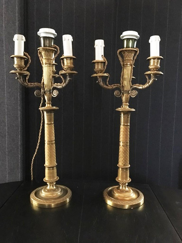 France late 18th Century handcrafted golden brass 4 lights candleholders or table lamps.  This magnificent pair of candleholders, was made in France. Fully handcrafted with fine  and elegant decor, they show at once the high-level house of