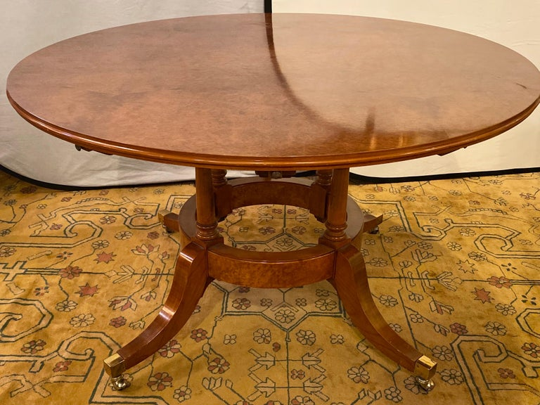 Francesco Molon Regency style dining center table by Giemme. Spectacular tortoise finished tabletop set on quad legged base having extension leafs measuring 11 inches each. The whole supported by brass casters on strong easy to move wheels. The