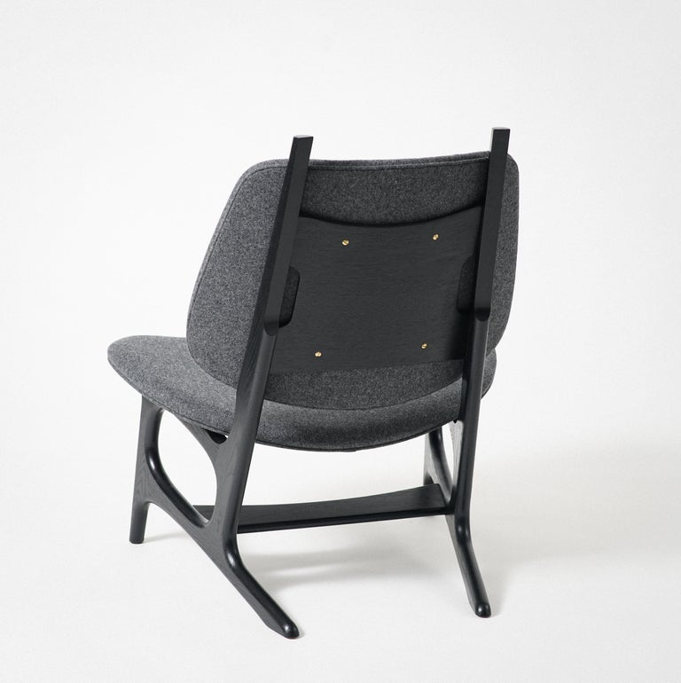 Phloem Studio Francis easy chair is a modern contemporary oversized easy chair with a exposed solid oak hardwood frame dyed black with an upholstered shell seat and back, with wool upholstery. The frames are handcrafted in walnut, maple or black.