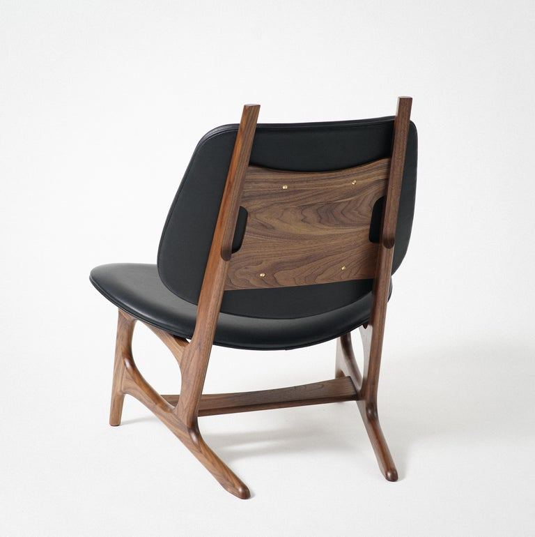 Phloem Studio Francis easy chair is a modern contemporary oversized easy chair with a exposed solid walnut hardwood frame with an upholstered shell seat and back, with leather upholstery. The frames are handcrafted in walnut, maple or black. Leather