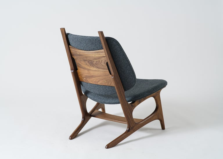 Phloem Studio Francis easy chair is a modern contemporary oversized easy chair with a exposed solid walnut hardwood frame with an upholstered shell seat and back, with wool upholstery. The frames are handcrafted in walnut, maple or black. Wool