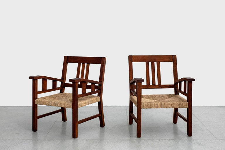 Classic wood and rope armchairs by French designer, Francis Jourdain, circa 1930.  Beautiful patina to wood and exceptional woven design. Newly woven seats and newly refinished.