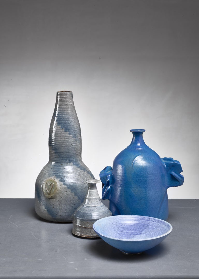 A set four ceramic pieces with a blue and grey glazing. The set consists of three vases and one bowl. The largest vase is 29 cm high with a 14 cm diameter. The bowl is 5 cm high with a 15 cm diameter.  The pieces are all marked by Agnese and in an