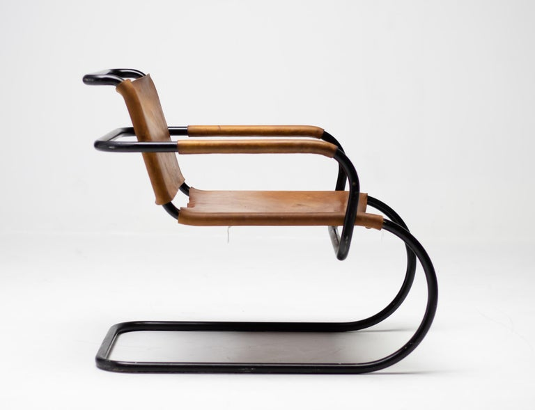 Tubular lounge chair designed by Franco Albini for the Triennale in Milan in 1933. The original black enameled frame emphasizes the graphic qualities of this design. The natural leather seat and back are still in nice, fully functional, vintage