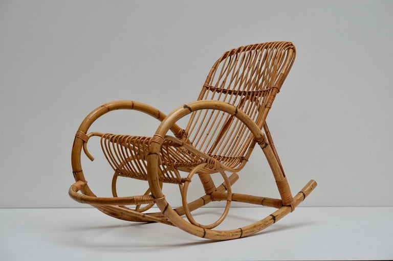 A rare Franco Albini style arm rattan rocking chair and features a steam bent bamboo frame.  This rare rocking chair was made in the late 1950s-1970s Great curves and good original condition.