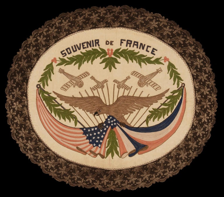 Franco-American textile with the image of an eagle supporting knotted and draped american and French flags beneath four war planes; embroidered silk floss and metallic bullion thread on a silk ground, with elaborate bullion fringe, made to celebrate