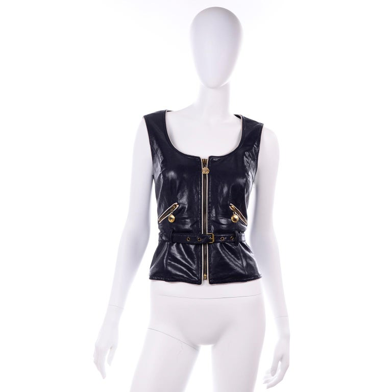 This is a wonderful vintage navy blue faux leather vest with white piping and gold hardware from Moschino Jeans. This collectible designer piece was made in Italy in the early 1990's.  There are two zip slash pockets on the front and a center zipper