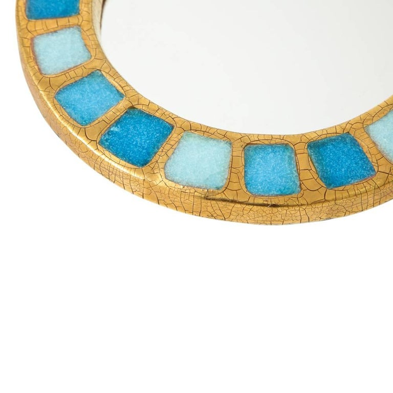 Francois Lembo ceramic mirror gold blue, France, 1970s. Medium scale round gold crackle glaze mirror decorated with a pattern of three tones of blue squares.  A native of Vallauris François Lembo started his pottery career in 1951 in the workshops