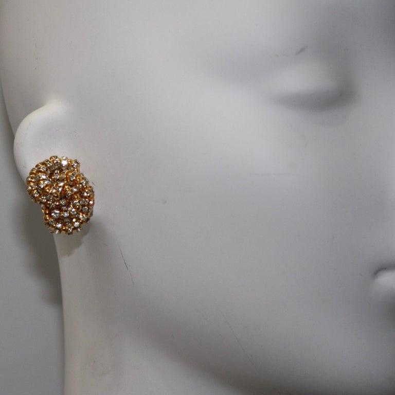 Swirls of Swarovski crystal rondelles set on gold metal.