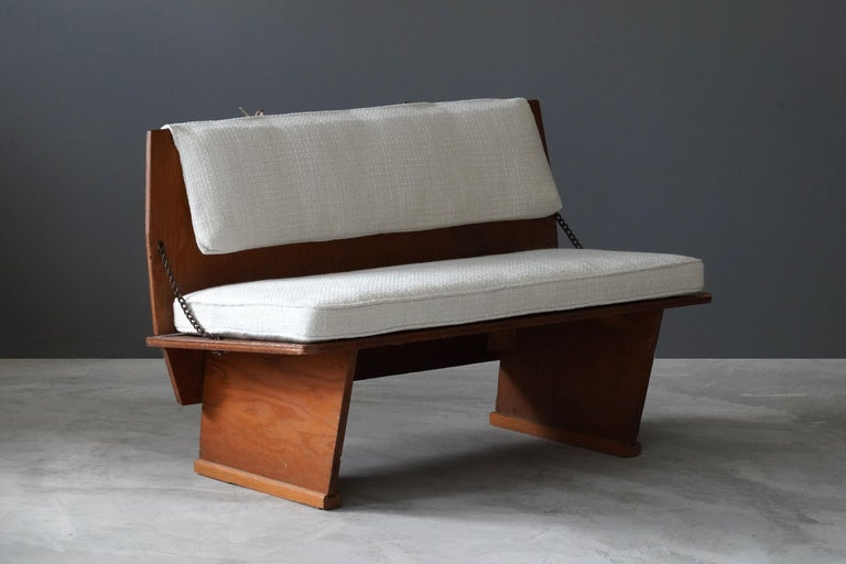 A rare bench / loveseat / settee designed by Frank Lloyd Wright produced by his Taliesin studio. Produced in limited numbers for Lloyd Wright's famous Unitarian Church in 1951. Marked.  Present bench is the rarer variation of two model benches