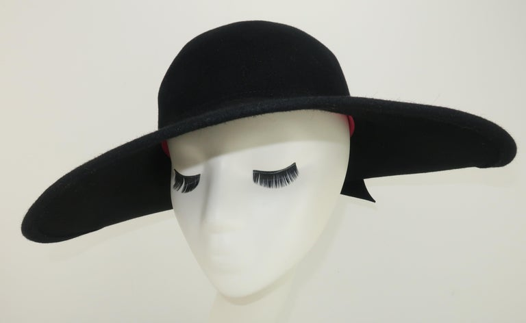 1980's Frank Olive black wool felt hat with a wide brim at the front tapering to an upturn at the back adorned by a felted bow.  Inside rim is lined with a hot pink grosgrain ribbon.  Reminiscent of 1920's styles but with a chic modern