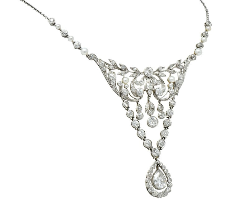 Centering a large station comprised of a scrolled foliate design with two extensions of tulip motif links terminating in a pear shaped articulated drop  Terminating in a pear shaped articulated drop, bezel set, with a pear cut diamond weighing
