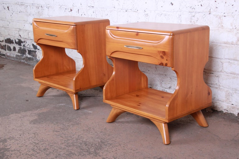 An exceptional pair of Mid-Century Modern sculptured pine nightstands or end tables by Franklin Shockey Co. The nightstands feature gorgeous knotty pine wood grain and a unique hourglass profile. They are extremely well made from solid pine. The