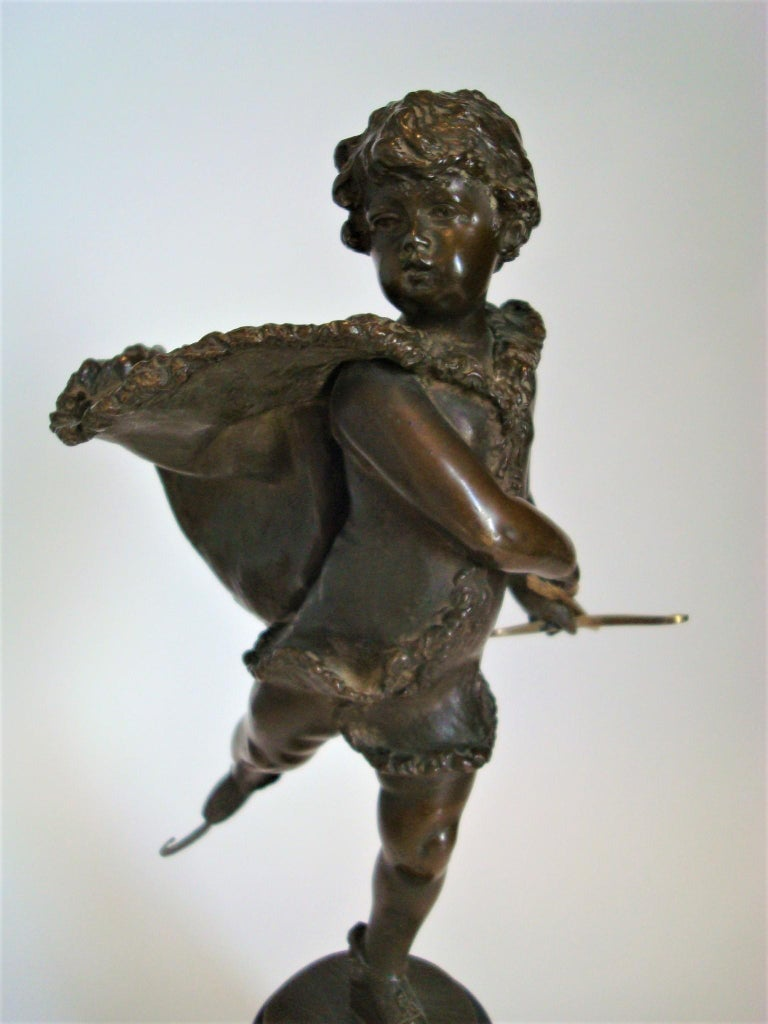 Bronze depicting a young boy (cupid) ice skating, by Franz Iffland (Berlin 1862-1935). A boy in fur-trimmed cape, holds a cupid-like feathered arrow with bow. Iffland was a member of the Berliner Bildhauerschule, was active 1885-1915. He became most