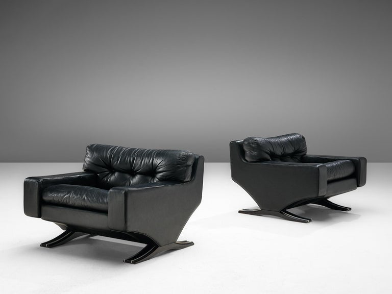 Franz Sartori for Flexform, pair of lounge chairs, leather and beech, Italy, 1960s  Sturdy pair of lounge chairs in black leather by the Italian sculptor Franz Sartori. These chairs feature a modern design due to the straight lines. The waved