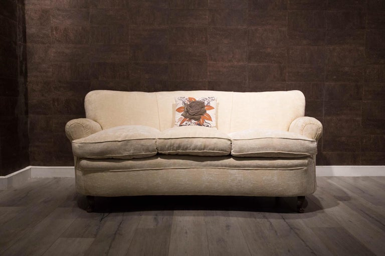 Originally upholstered in blue-green velvet, it was later re-upholstered in elegant beige-white cotton.  The two armrests are rounded, the backrest is slightly curved, and it has three comfortable cushions.   Four rounded walnut legs.  The