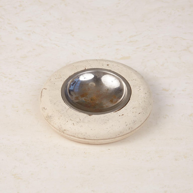 A tire shaped round travertine ashtray by Fratelli Mannelli, Italy, circa 1970s, has a honed to a matte finish and with a scooped metal dish that sits in a recess in its center. It has a groove carved around its circumference at the apex of its