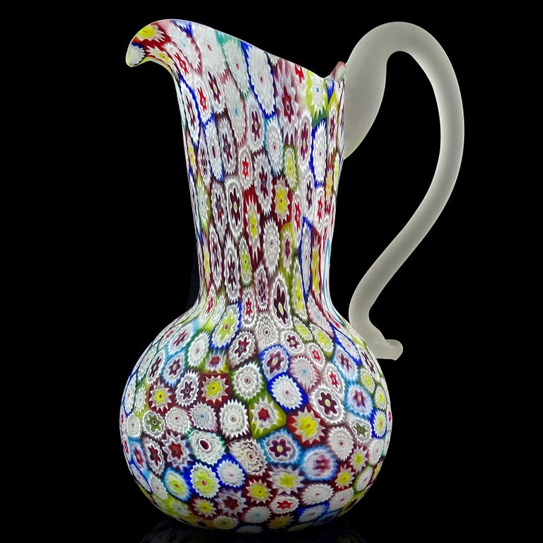 Beautiful vintage Murano hand blown millefiori, rainbow colors, flower mosaic Italian art glass pitcher / vase. Documented to the Fratelli Toso Company. The piece has a great array of colors, with white, cobalt blue, sky blue, green, yellow, bright