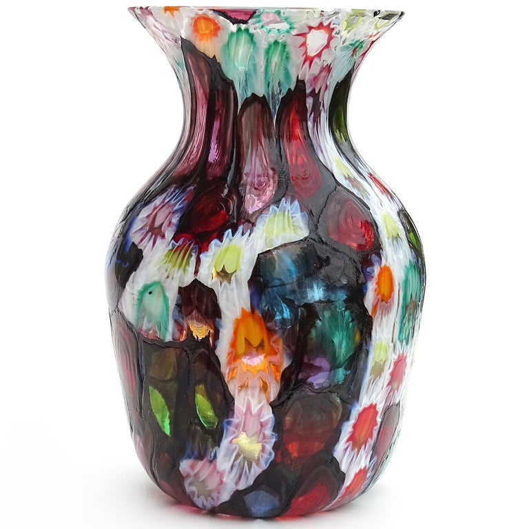 Beautiful Murano hand blown multi-color Millefiori flowers or stars mosaic Italian art glass flower vase. Documented to the Fratelli Toso company. Many of the murrines are lined in metallic black, like stained glass windows. Has blue, red, pink,