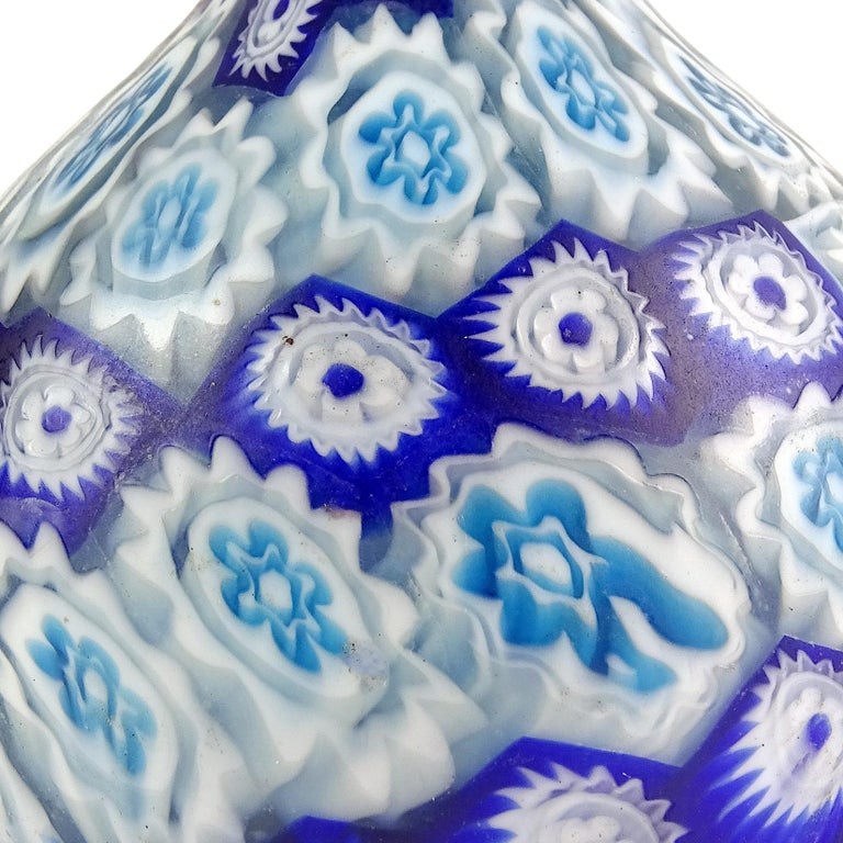 Beautiful antique Murano hand blown millefiori mosaic Italian art glass decorative cabinet vases. Documented to the Fratelli Toso company. The first has orange, yellow, white and blue flowers, with ornate handles. The second has horizontal cobalt
