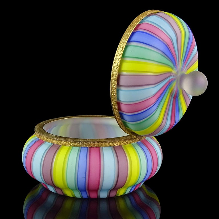 Beautiful Murano hand blown satin surface, rainbow ribbons, Italian art glass vanity jewelry box. Documented to designer Fratelli Toso. It has cobalt blue, yellow, green, pink, purple and light blue stripes. The inside is white, and has gold colored