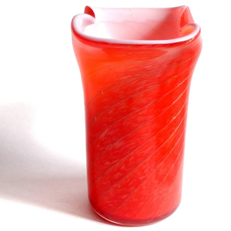 Beautiful vintage Murano hand blown bright red over white and copper aventurine Italian art glass flower vase. Documented to the Fratelli Toso company. Published. The piece has a candy cane swirl and glitters in the light. Midcentury era. Measures 6