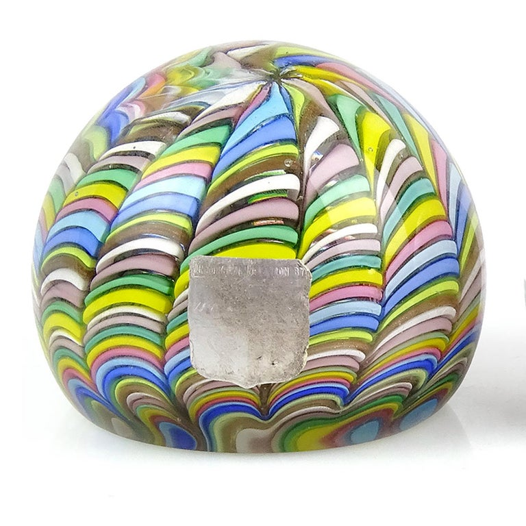 Beautiful vintage Murano hand blown rainbow stripe ribbons Italian art glass paperweight. Documented to the Fratelli Toso Company. It has alternating pink, white, blue, aqua, green, yellow, orange, and copper aventurine stripes. There is a worn