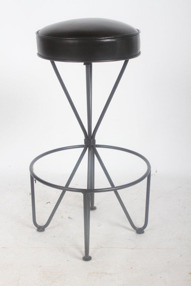 Single Frederick Weinberg circa 1950s swivel bar stool, refinished wrought iron base and black graphite leather seat. Light use, restored 4 years ago. Seat is 14