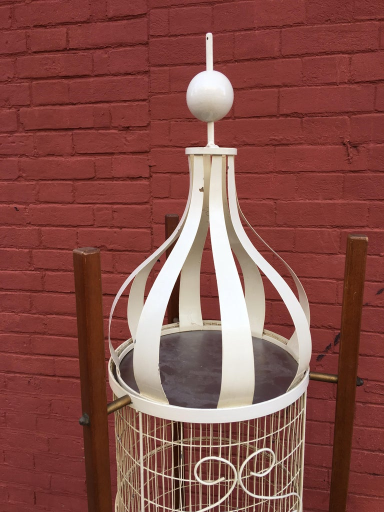 Frederick Weinberg Standing Birdcage. Three upright wood poles holds a wire cage afloat. Whimsical Design with large ball finale top and ball cage door knob.