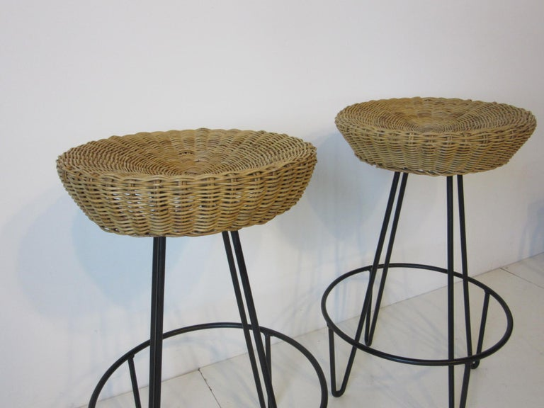A pair of welded iron based bar stools with foot rests and woven wicker seats a great addition for that tiki bar or casual entertaining area. The measurement for the footrest ring is 18