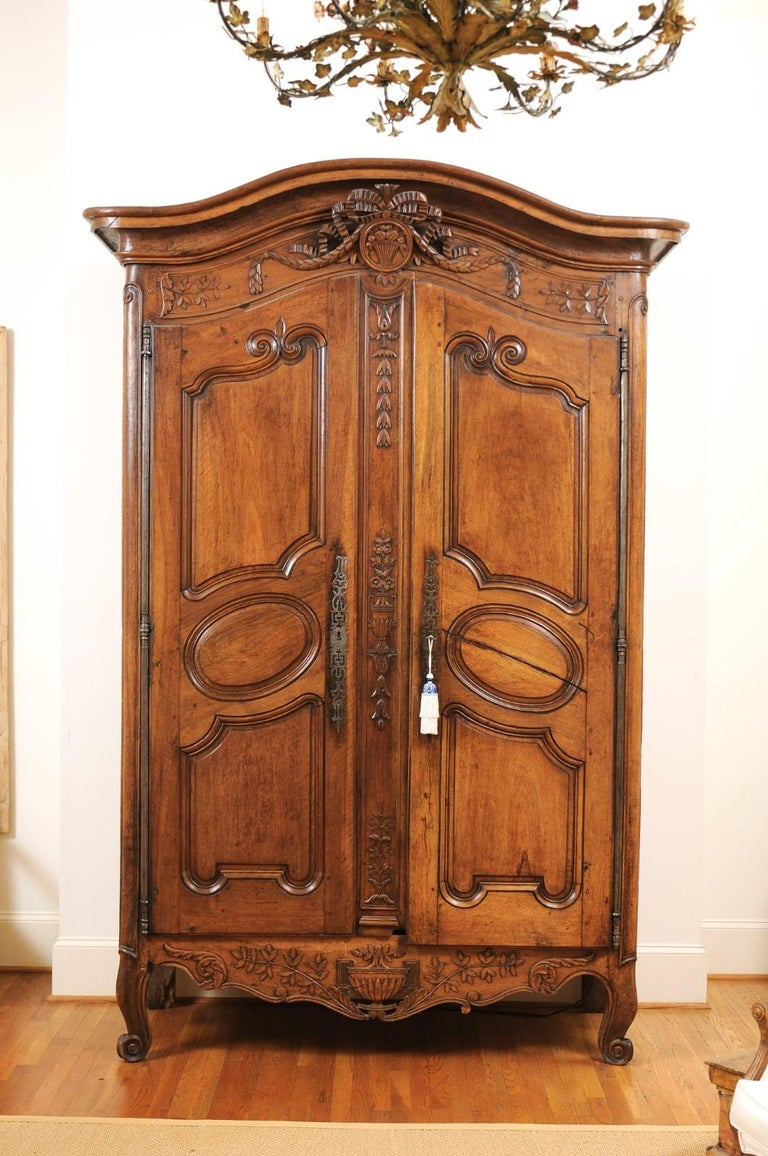 A French Louis XV period mid-18th century bonnet top walnut armoire from Nice, with ribbon-tied medallion and carved foliage. Handmade in Southern France during the reign of King Louis XV nicknamed the Bien-Aimé (the Beloved), this Niçoise walnut