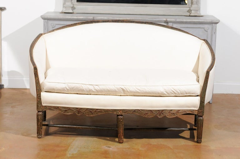 A French Louis XVI period Provençal painted sofa from the late 19th century, with new upholstery, fluted legs and side stretchers. Born in Provence during the reign of King Louis XVI, this French painted sofa features an arched back, connected to