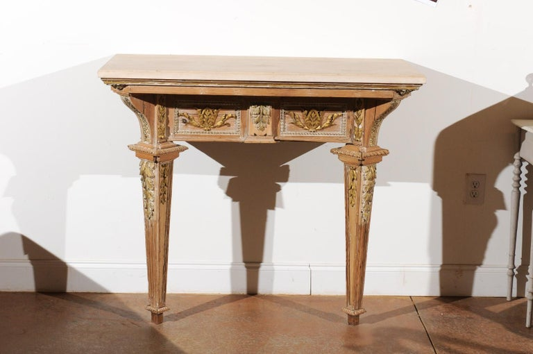 A French Louis XVI period hand carved and parcel-gilt wooden console table from the late 18th century, with new custom-made limestone top and tapered legs. Born in France during the reign of the last monarch of the Ancien Régime, this console table