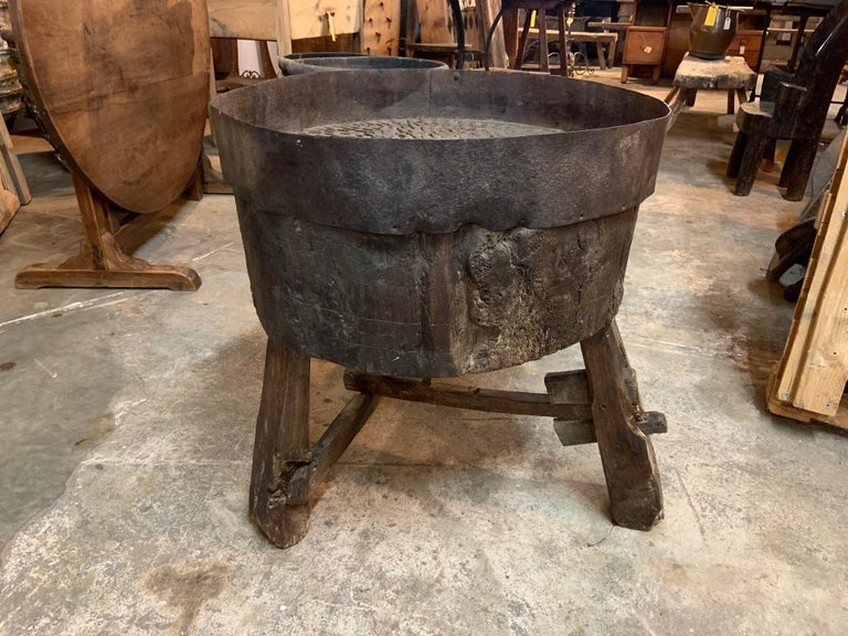 A sensational Arte Populaire Billot used for grinding grains, corn, wheat, etc. It is constructed from a massive billot, chopping block with an iron band around the top so that ground grains would not fall off. There are many iron pieces embedded