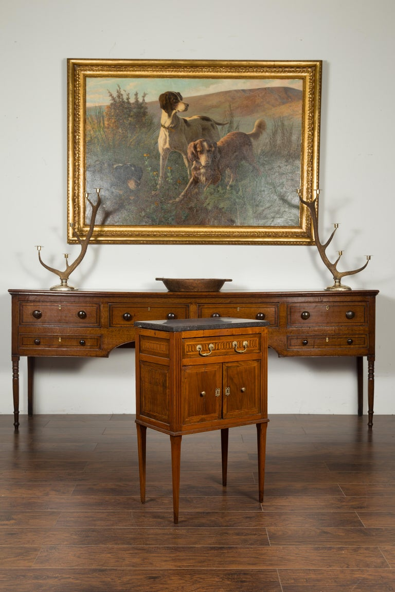 A French neoclassical period walnut side table from the early 19th century, with marquetry decor and dark grey marble top. Created in France during the early years of the 19th century, this walnut side table features a dark grey marble top sitting