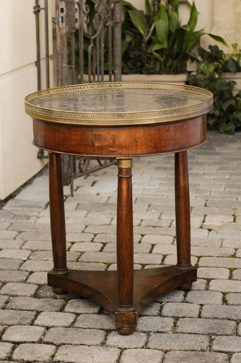 A French period Empire walnut guéridon side table from the early 19th century, with grey marble top and bronze mounts. Born in the first quarter of the 19th century under the reign of France's first Emperor Napoleon I, this exquisite guéridon