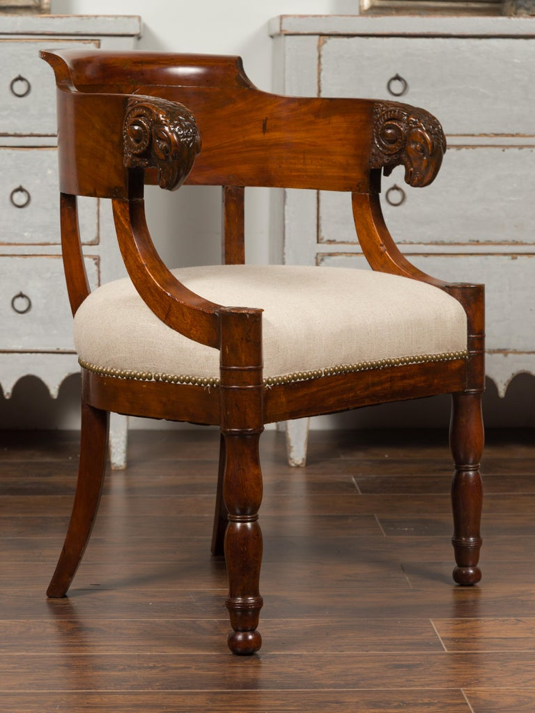A French Restauration mahogany armchair from the 19th century, with carved rams' heads and new upholstery. Born in France during the Restauration period, this mahogany armchair features a wraparound back adorned with exquisitely carved rams' heads.