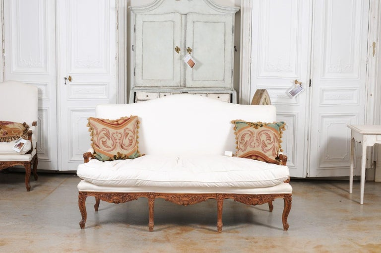 A French Régence style carved wood canapé from the mid-19th century, with new upholstery. Created in France in the early years of Emperor Napoleon III's reign, this Régence style three-seat sofa features a slightly slanted camelback, flanked with