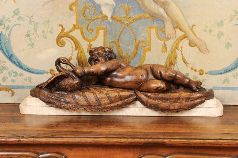 A French carved walnut putto feeding a swan sculpture from the late 19th century, with marble base. Created in France during the last quarter of the 19th century, this walnut sculpted group features a chubby putto laying on his side and extending