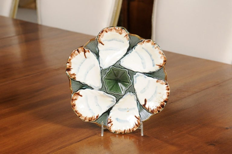 A French glazed Majolica Longchamp Terre de Fer oyster plate from the late 19th century, with central flower. We have two available, priced and sold $295 each. Created in France during the last decade of the 19th century, this oyster plate features