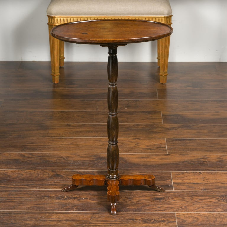 A French walnut guéridon table from the late 19th century, with oval top and turned pedestal base. Crafted in France during the last quarter of the 19th century, this walnut side table features an oval top with slightly raised edges, sitting above a